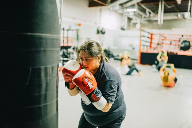 Woman hitting boxing bag with determined stare