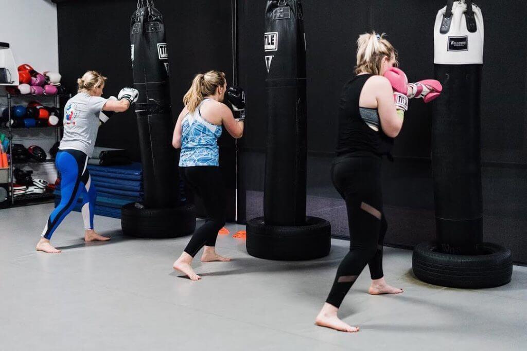 Women hitting boxing bags
