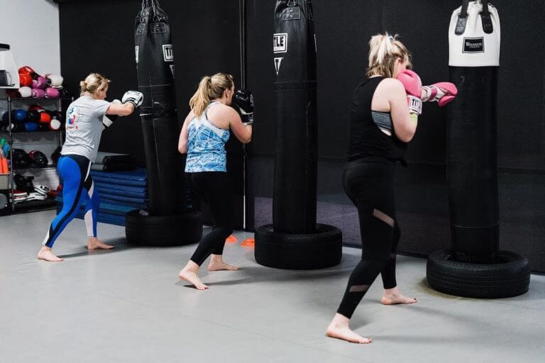Women hitting boxing bags